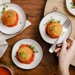 overhead view of small plates with crispy fried mashed potato balls with marinara sauce
