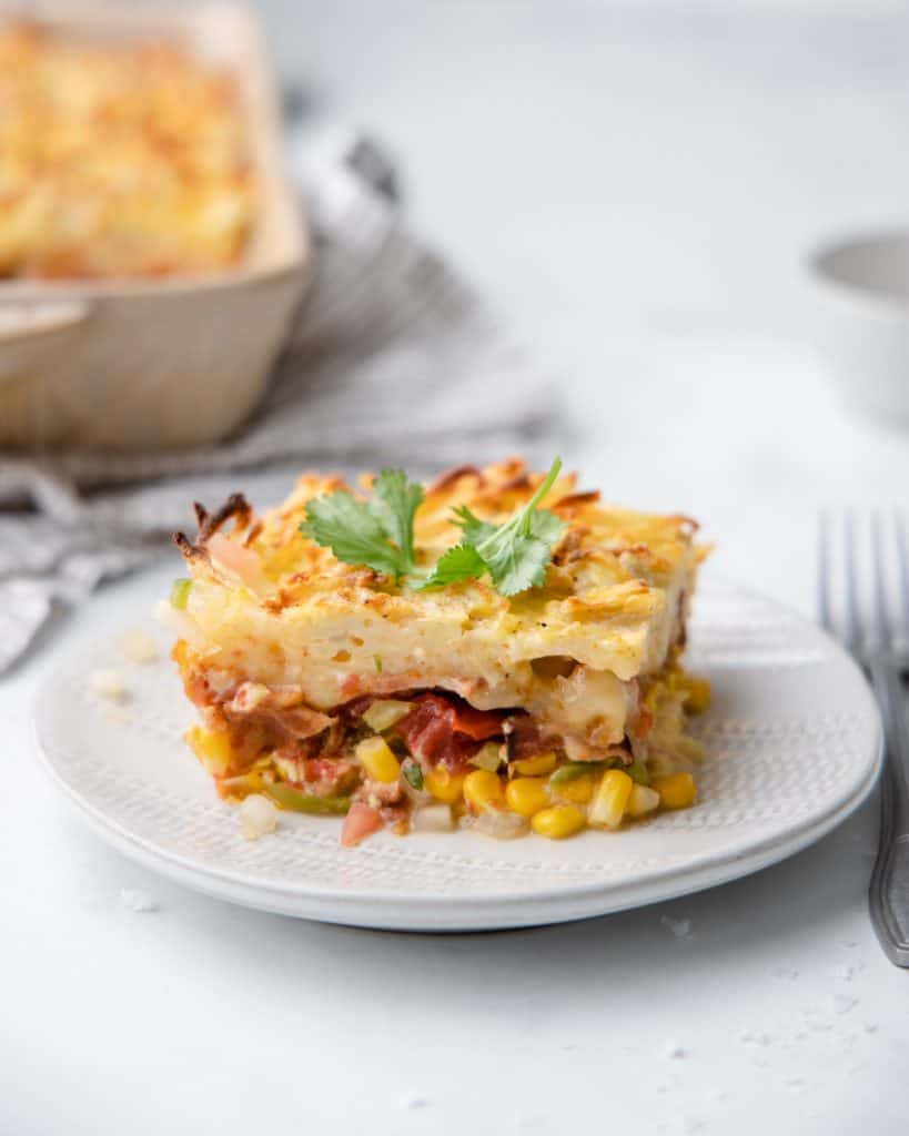 A piece of casserole with corn, bacon and shredded potatoes on a white plate with a fork and salsa.
