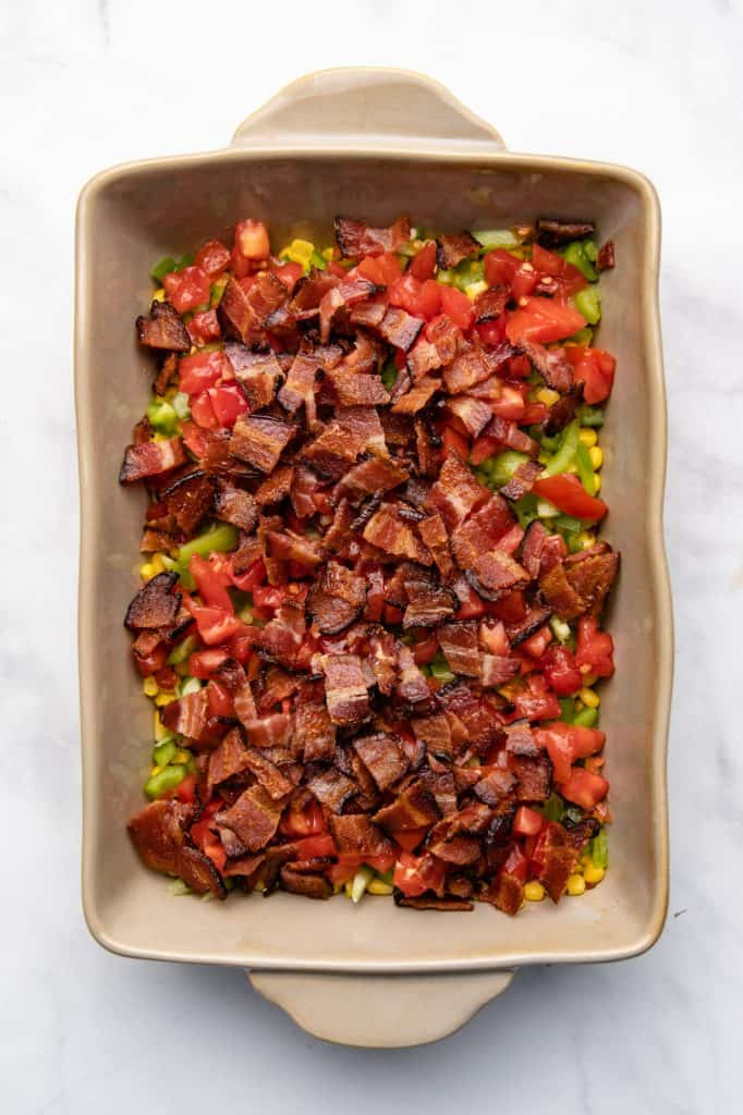 Corn and peppers and tomatoes and bacon in a casserole dish