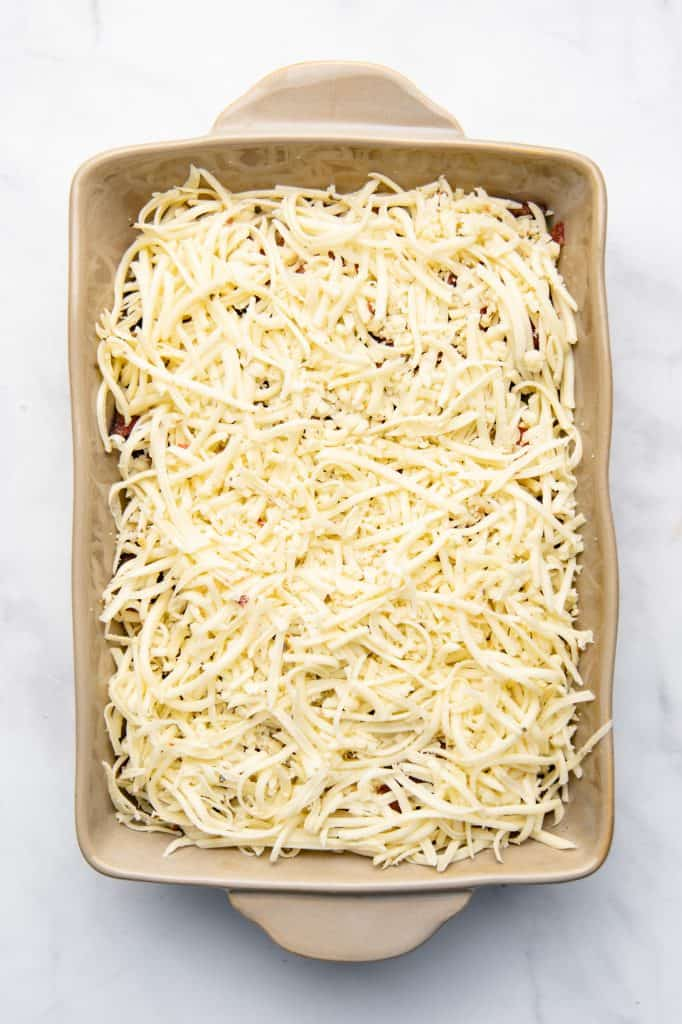 A casserole dish topped with cheese prior to baking