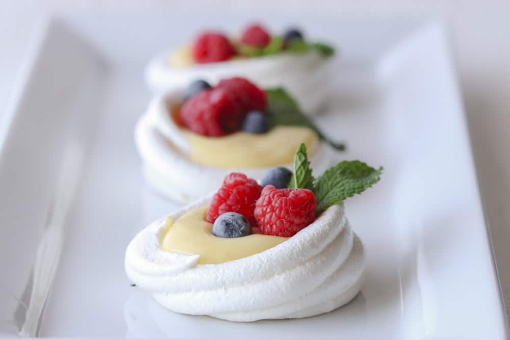 Three white meringue nests on  plate with lemon curd and fresh berries
