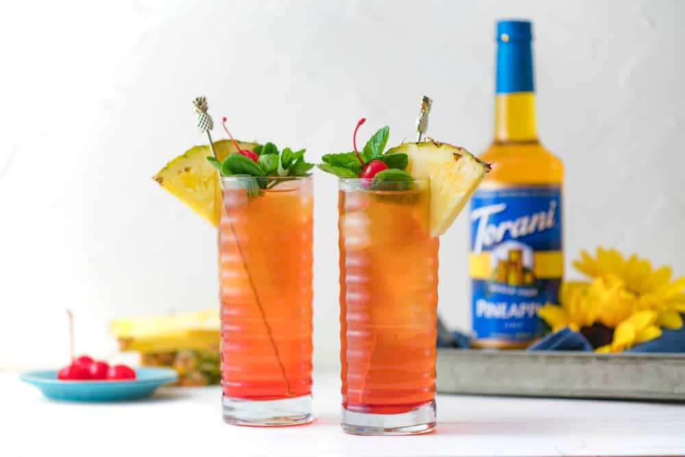 two tall glasses of iced tea with pineapple, cherry and mint garnish