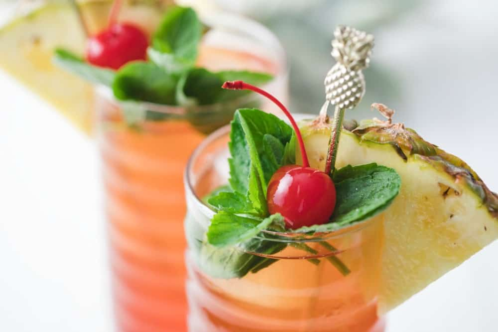 A festive iced tea drink with pineapple, cherry and mint