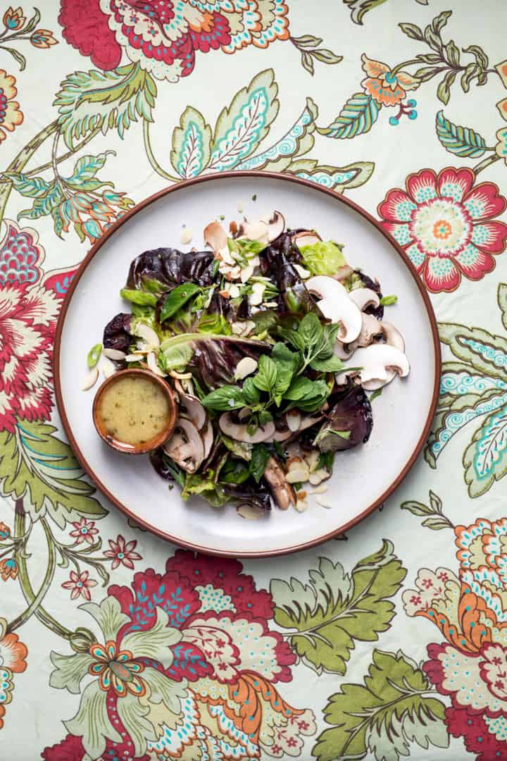 Salad with mushrooms and butter lettuce on a white plate and a floral tablecloth with mustard vinaigrette