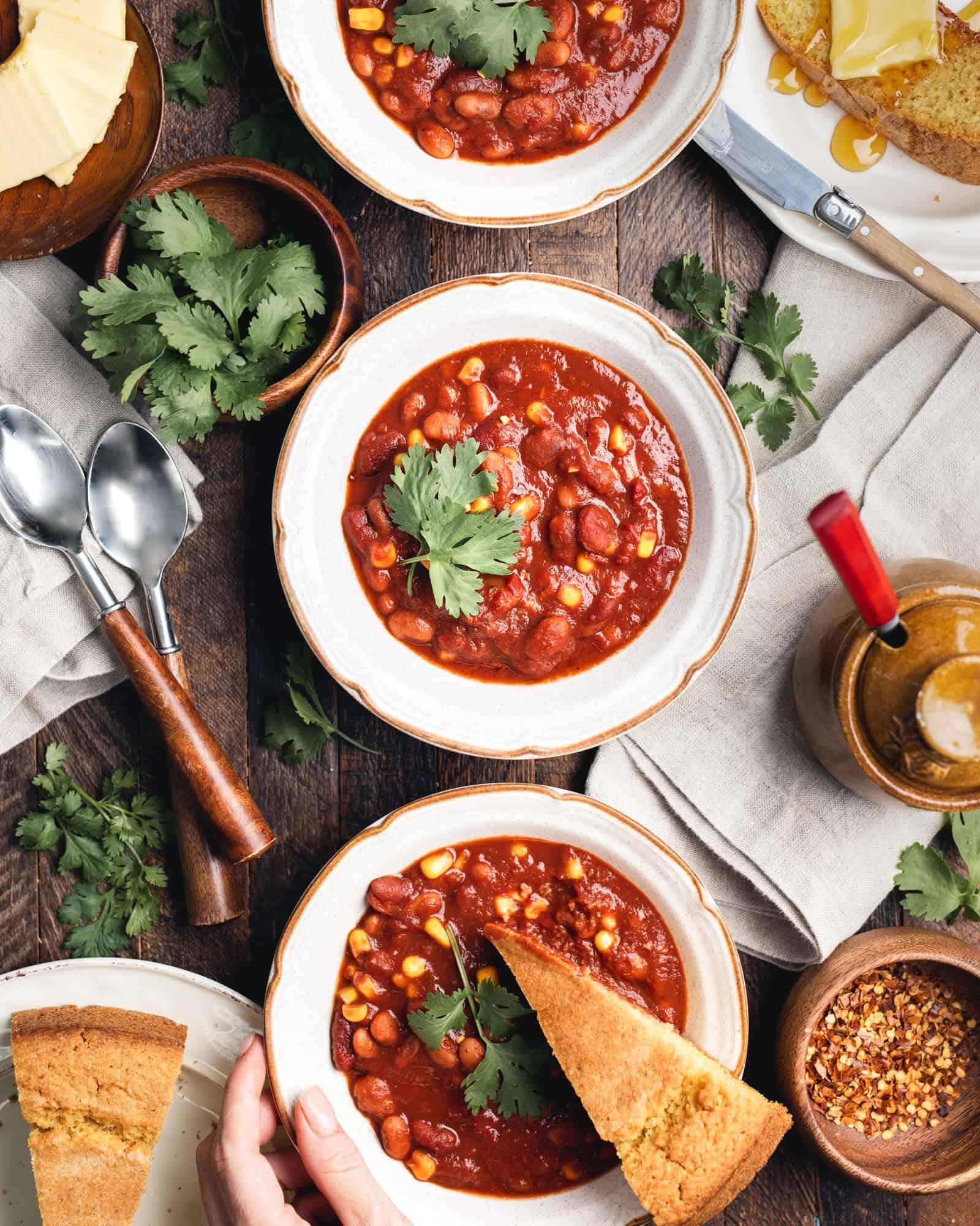 Vegan Chili in three bowls with cornbread and honey