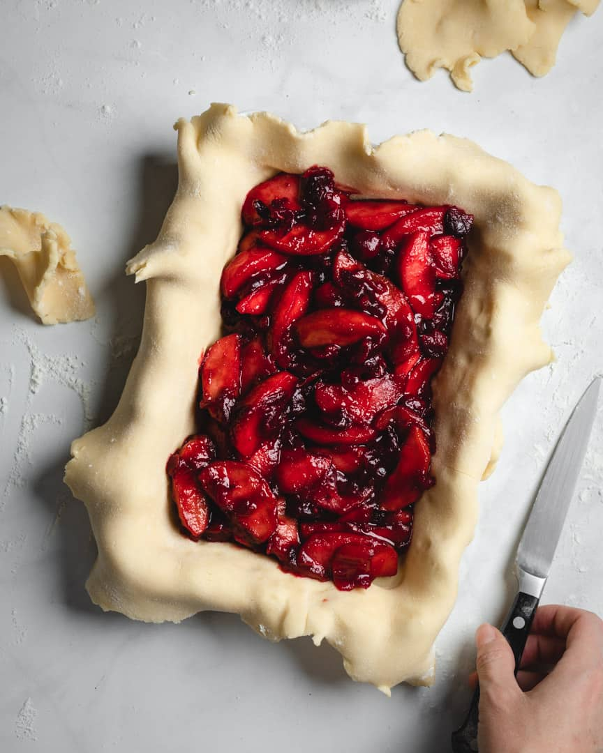 assembling pie with cranberry apple filling