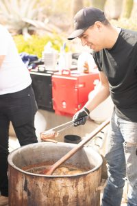 Chef pulling a piece of meat from a large pot