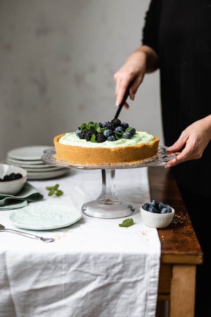 slicing into a pistachio tart on a wooden table with a white table cloth