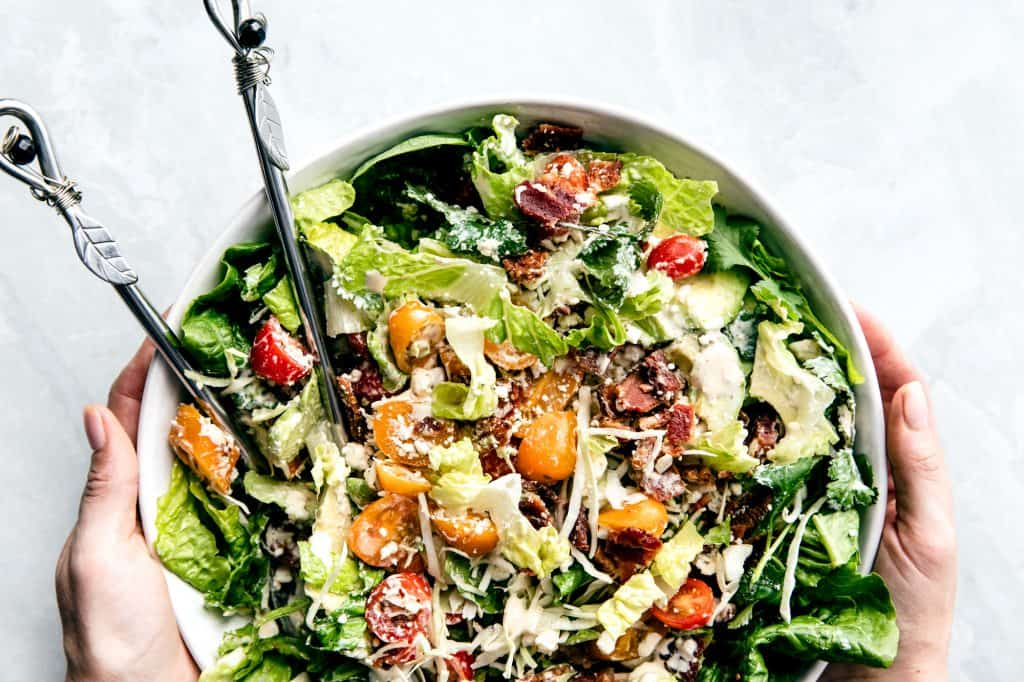 A large green salad with tomatoes, avocado, cheese and bacon in a large bowl placed on a marble countertop, tossed tossed with the tongs on the left