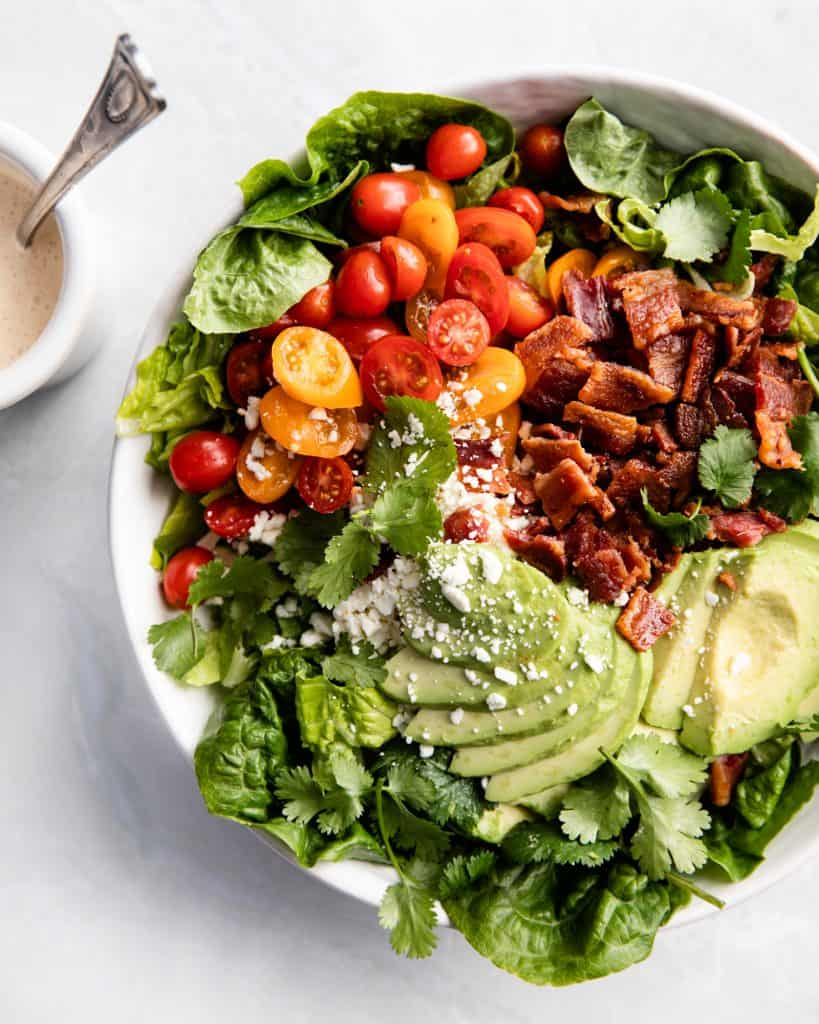 A large green salad with tomatoes, avocado, cheese and bacon in a large bowl placed on a marble countertop, dressing on the side