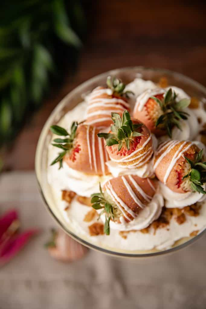 Overhead view of a trifle dish filled with homemade carrot cake, cream cheese whip and vanilla pudding topped with more whipped cream and dipped strawberries