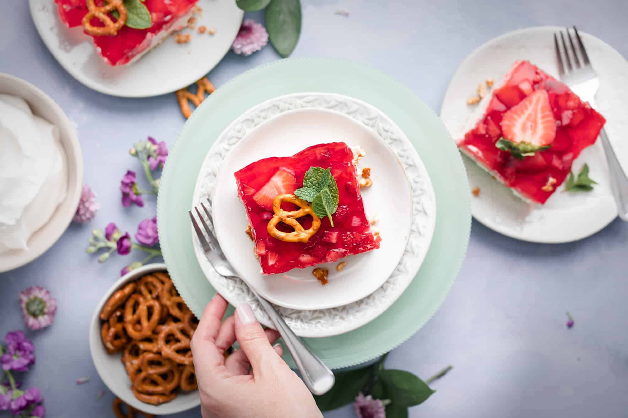 a plate with a dessert topped with strawberry jello and garnished with a pretzel