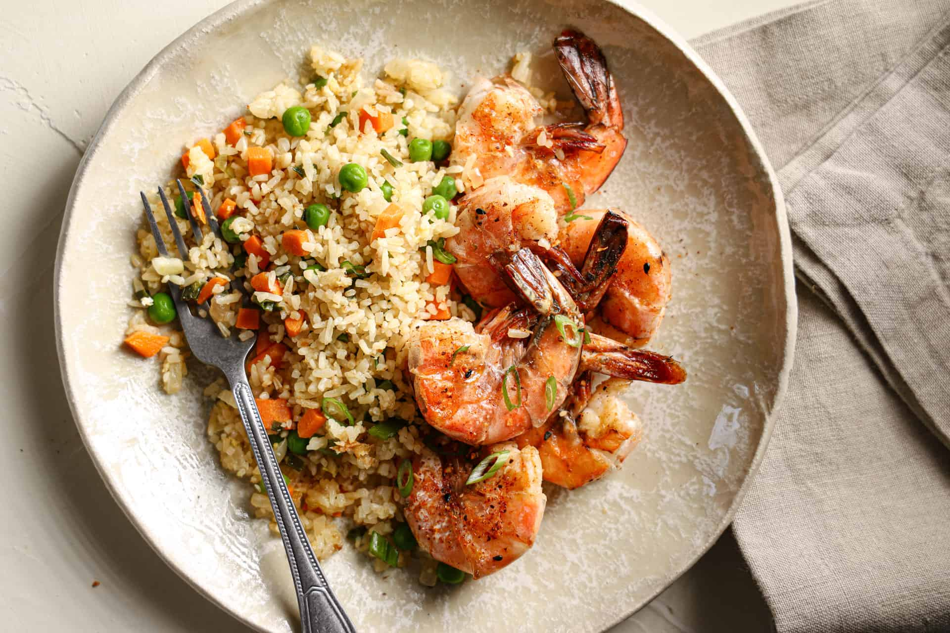 Shrimp and fried rice on a tan plate with a napkin and fork