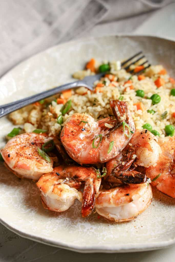 View of a plate of shrimp with fried rice and scallions